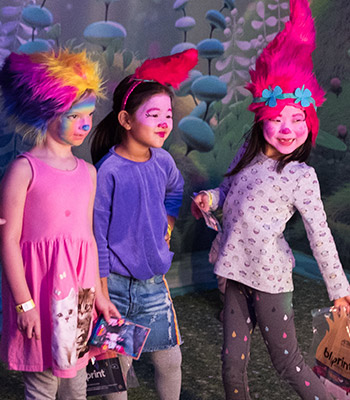 Three friends with Trolls wigs and face paint take a selfie together at Trolls the Experience