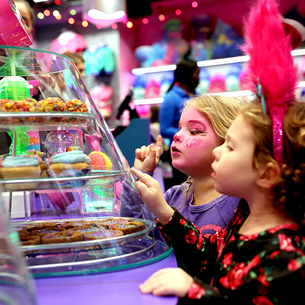 Two adorable little girls in Trolls makeup looking at the dessert display inside the Cupcakes & Rainbows Cafe